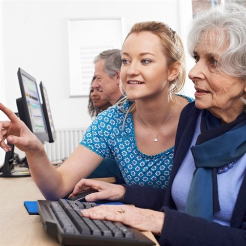 Young person helping senior woman with computer